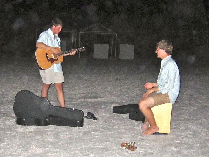 Listening to performers on the beach.