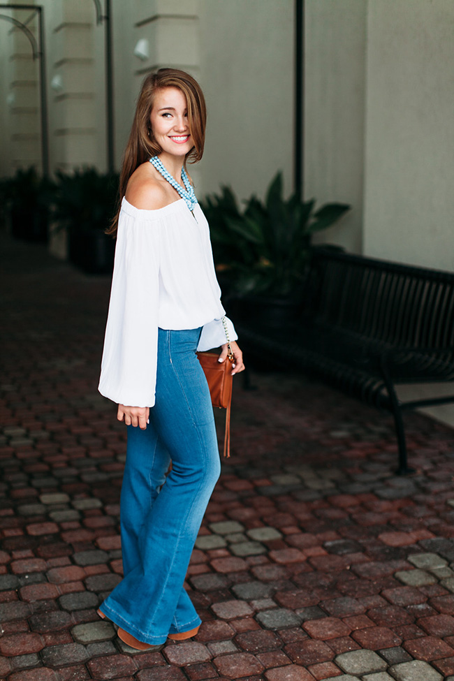 bell bottom jeans, tassel crossbody, off the shoulder long sleeved top, akola project collar, seventies style, southern girl style, lace up platforms