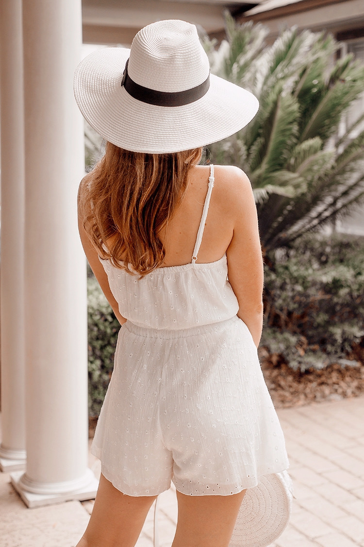 white romper, wide brimmed panama hat, white straw bag